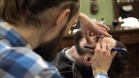 Профессиональная борода ` s клиента бритья парикмахера с прямой бритвой очень сконцентрированный 4K сток-видео