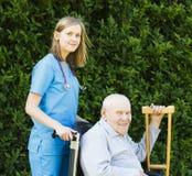 Профессиональная помощь для пожилых людей в кресло-коляске Стоковая Фотография RF