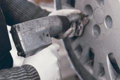 Профессиональное колесо автомобиля механика автомобиля изменяя Стоковые Фотографии RF