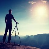 Профессиональное пребывание фотографа с треногой на скале и думать Мечтательный ландшафт fogy, голубой туманный восход солнца в к стоковая фотография