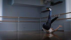 Профессиональное breakdancer выполняет сложную тренировку танца на поле студии танца Молодой мальчик закручивая на сток-видео