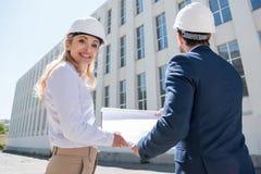 Профессиональные архитекторы в защитных шлемах держа светокопию пока работающ на строительной площадке Стоковое фото RF
