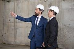 Профессиональные архитекторы в защитных шлемах обсуждая проект и смотря прочь Стоковое фото RF
