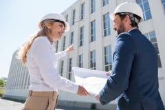 Профессиональные архитекторы в защитных шлемах обсуждая светокопию пока работающ на строительной площадке Стоковые Фото