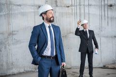 Профессиональные архитекторы в шлемах обсуждая проект на строительной площадке Стоковая Фотография