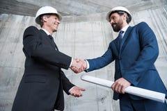 Профессиональные архитекторы в шлемах тряся руки и усмехаясь один другого Стоковое Фото