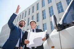 Профессиональные архитекторы при светокопия стоя близко автомобиль и смотря прочь Стоковая Фотография