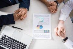 Профессиональные бизнесмены обсуждая диаграммы на рабочем месте Стоковые Фото
