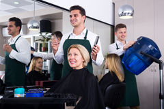 Профессиональные волосы вырезывания стилизатора пожилой блондинкы Стоковое Изображение