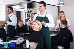 Профессиональные волосы вырезывания стилизатора пожилой блондинкы Стоковое Фото