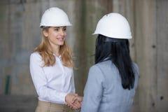 Профессиональные инженеры в защитных шлемах тряся руки и смотря один другого Стоковые Фото