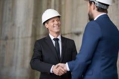 Профессиональные инженеры в защитных шлемах тряся руки и смотря один другого Стоковая Фотография