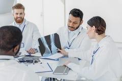 Профессиональные домашние врачи обсуждая рентгенограмму Стоковые Фото