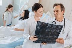 Профессиональные опытные доктора смотря фото рентгеновского снимка Стоковые Фото