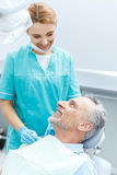 Профессиональный дантист и зрелый пациент смотря один другого в зубоврачебном офисе Стоковые Изображения RF