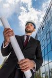 Профессиональный архитектор в трудной шляпе держа светокопию и смотря прочь Стоковая Фотография RF