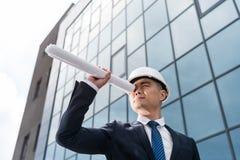 Профессиональный архитектор в трудной шляпе смотря через светокопию в руке Стоковое Изображение RF