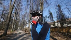 Профессиональный велосипедист говорит телефоном в парке акции видеоматериалы