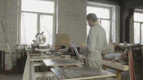 Профессиональный взрослый плотник проверяя результат работы Отполированные доски отрезка деревянные сток-видео