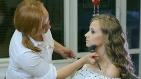 Профессиональный визажист очищает вверх сторону женщины с косметической щеткой сток-видео