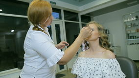 Профессиональный визажист прикладывая веко молодой женщины блеска глаза видеоматериал