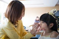 Профессиональный визажист работая с милым азиатским ребенком Стоковое Изображение RF