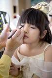 Профессиональный визажист работая с милым азиатским ребенком Стоковая Фотография RF
