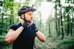 Профессиональный всадник горного велосипеда, велосипедист подготавливая шлем защиты во время разминки Стоковое фото RF