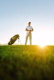 Профессиональный игрок в гольф стоя на поле на заходе солнца стоковая фотография rf