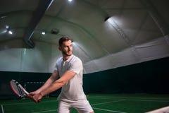 Профессиональный игрок играя теннис в крытом суде Стоковые Фото