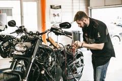 Профессиональный механик мотоцикла работая в ремонтных услугах велосипеда Стоковые Изображения
