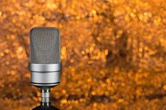 Профессиональный микрофон на оранжевой предпосылке из фокуса Стоковое фото RF