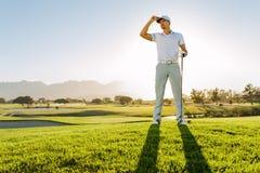 Профессиональный мужской игрок в гольф стоя на поле для гольфа Стоковое фото RF
