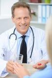 Профессиональный доктор давая пилюльки Стоковая Фотография RF