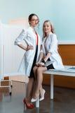 Профессиональный доктор сидя на таблице с компьтер-книжкой с коллегой Стоковое Фото