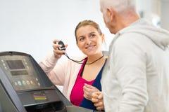 Профессиональный тренер фитнеса помогая пожилому клиенту Стоковые Изображения RF