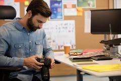 Профессиональный фотограф используя камеру в творческом офисе Стоковая Фотография