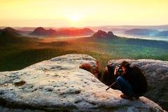 Профессиональный фотограф с треногой на скале и думать Мечтательный ландшафт fogy, туманный восход солнца в красивой туманной дол стоковые фотографии rf