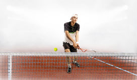 Профессиональный человек держа ракетку и шарик тенниса пока тренирующ стоковое изображение