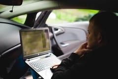 Профессиональный человек с компьтер-книжкой в автомобиле настраивает настраивая систему управления, уточняющ программное обеспече Стоковая Фотография RF