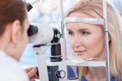 Профессиональный oculist проверяет человеческое зрение с оборудованием Стоковое Изображение RF