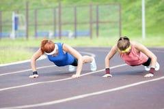 2 профессиональных спортсменки делая отжимать поднимают на месте спорта Стоковые Фотографии RF