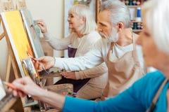 3 профессиональных художника тратя время в студии картины Стоковое Изображение