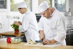 2 профессиональных шеф-повара подготавливая овощи в большой кухне Стоковое Фото
