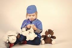 Профессия ветеринара Ребенок в ветеринаре доктора равномерном играя с животным игрушки Стоковая Фотография RF