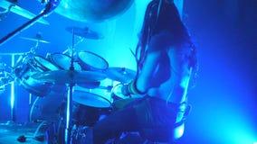 Профиль непознаваемого профессионального барабанщика держа деревянные drumsticks и ударяя на наборе барабанчика во время рок-конц акции видеоматериалы