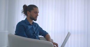Профиль снятый прогрессивного фрилансера печатая на ноутбуке сидя в кресле в светлых поворотах офиса к камере и дозорам акции видеоматериалы
