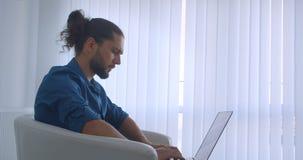 Профиль снятый прогрессивного фрилансера печатая на ноутбуке сидя в кресле в светлых поворотах офиса к камере и дозорам сток-видео