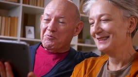 Профиль снятый старшей кавказской беседы пар в онлайн videochat с их друзьями на планшете смеясь на уютном доме видеоматериал