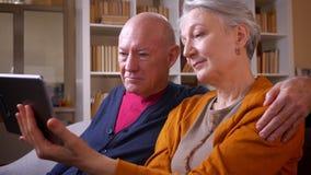 Профиль снятый старших кавказских супругов наблюдает в планшет быть позабавленный сидеть на софе в живя комнате сток-видео